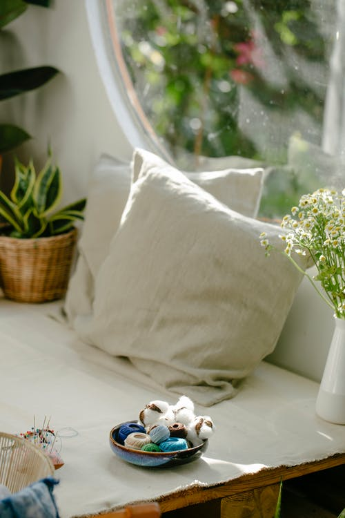 Colorful threads in bowl placed near pillows and flowers