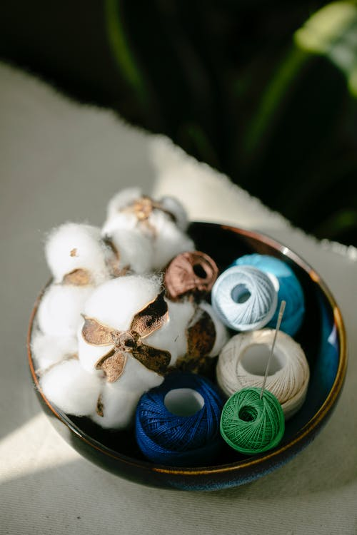From above of set of colorful silk thread bobbins placed in bowl with natural cotton balls in atelier