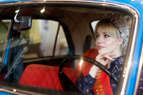 Though window view of young female driver in stylish clothes with red ribbon on shoulder and crown sitting in retro car and looking away