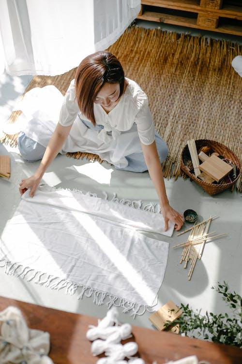 Ethnic artisan preparing fabric for shibori on floor
