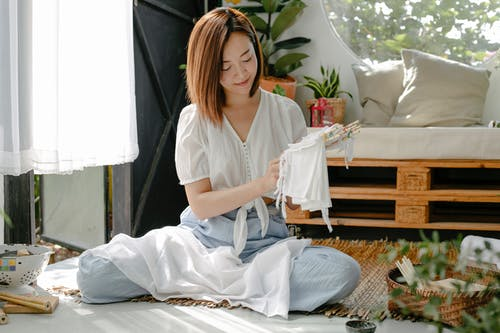Young content Asian craftswoman wrapping cloth around poles with threads while demonstrating Japanese tie dye technique at home