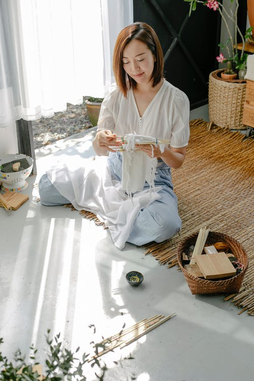 Asian craftswoman wrapping cotton fabric around poles while showing traditional Japanese tie dye technique in house on sunny day