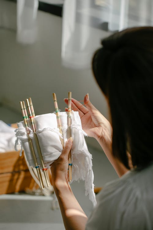 Back view of crop anonymous craftswoman wrapping cotton cloth around poles with threads while demonstrating shibori technique in sunlight