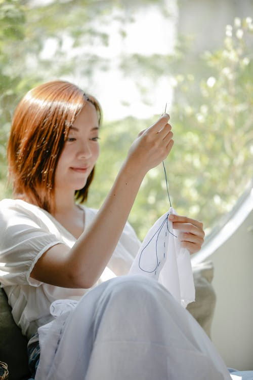 Content Asian craftswoman stitching cotton cloth with thread and needle while demonstrating tie dye technique at home in sunlight