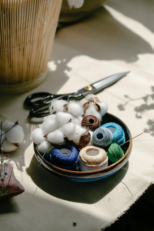 Thread bobbins with scissors and needles placed on table in atelier