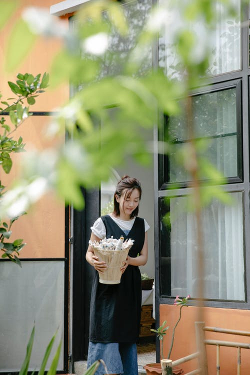Positive young Asian female in long skirt and apron standing near opened door and holding basket