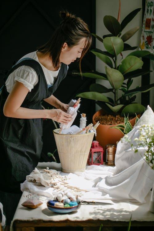 Asian female artisan preparing textiles for tie dye technique at home