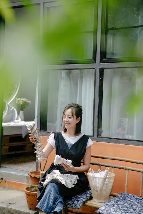Cheerful ethnic artisan with fabrics for shibori in patio