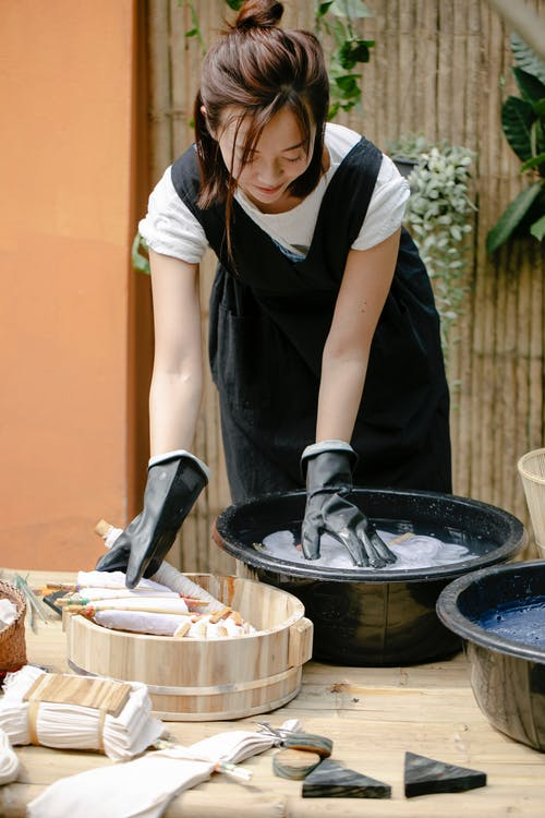 Asian craftswoman in gloves with cotton textiles and basins full of water showing Japanese tie dye techniques outdoors