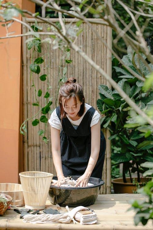 Asian female artisan with fabrics in basin showing shibori technique