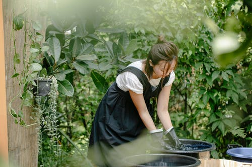 Young ethnic female artisan in gloves demonstrating shibori technique while painting cloth in basin with water in garden