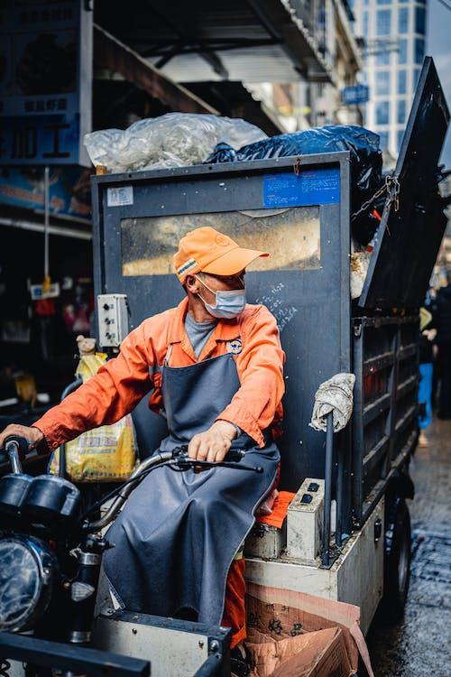 Man in Orange Jacket and Brown Hat Sitting on Black Motorcycle