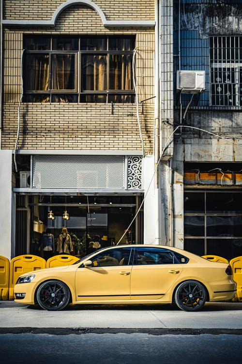 Yellow Car Parked Beside Building