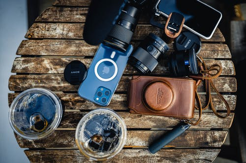 Blue and Black Camera Beside Black and Silver Dslr Camera