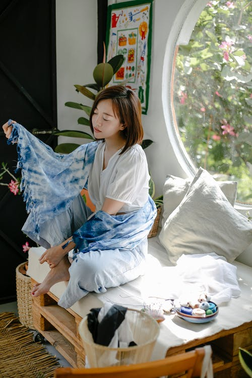 Young ethic female designer wrapped in dying cloth sitting with crossed legs in workshop for sewing handmade fabrics
