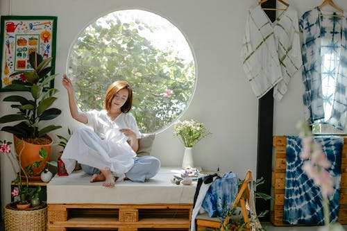 Full body of ethnic barefoot young lady in casual outfit sitting on seat at home while sewing white fabric near window and decorative elements