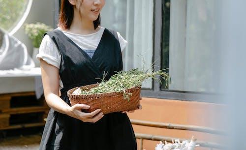 Crop craftswoman with plant sprigs for shibori technique