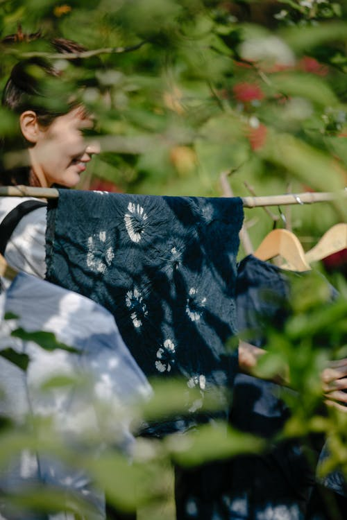 Side view of content Asian craftswoman hanging painted textiles with floral ornament in sunlight outdoors