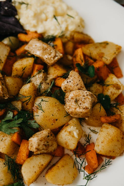 Delicious dish with fried potatoes and carrots served with herbs