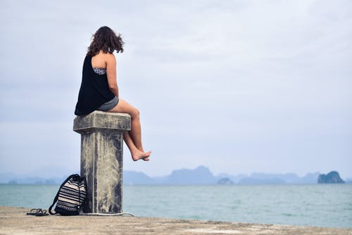 Woman in Black Shirt Sitting Near Body of Water during Daytime