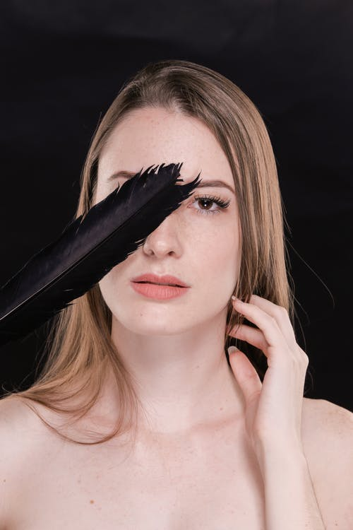 Woman With Blonde Hair Holding Black Feather