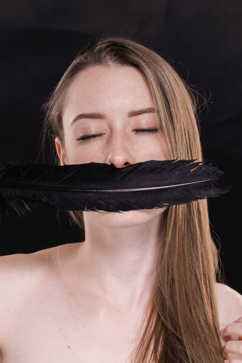 Woman Covering Her Face With Black Feather