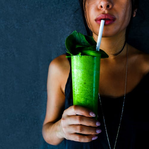 Woman in Black Tank Top Holding Green Plastic Cup