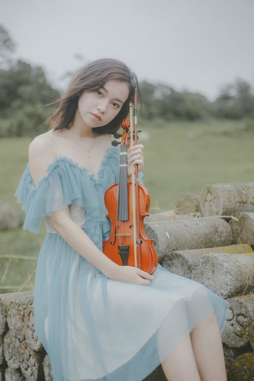 Woman in White Dress Playing Violin