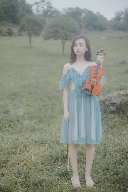 Girl in Blue Dress Holding Violin