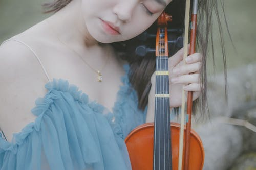 Woman in White Dress Holding Violin