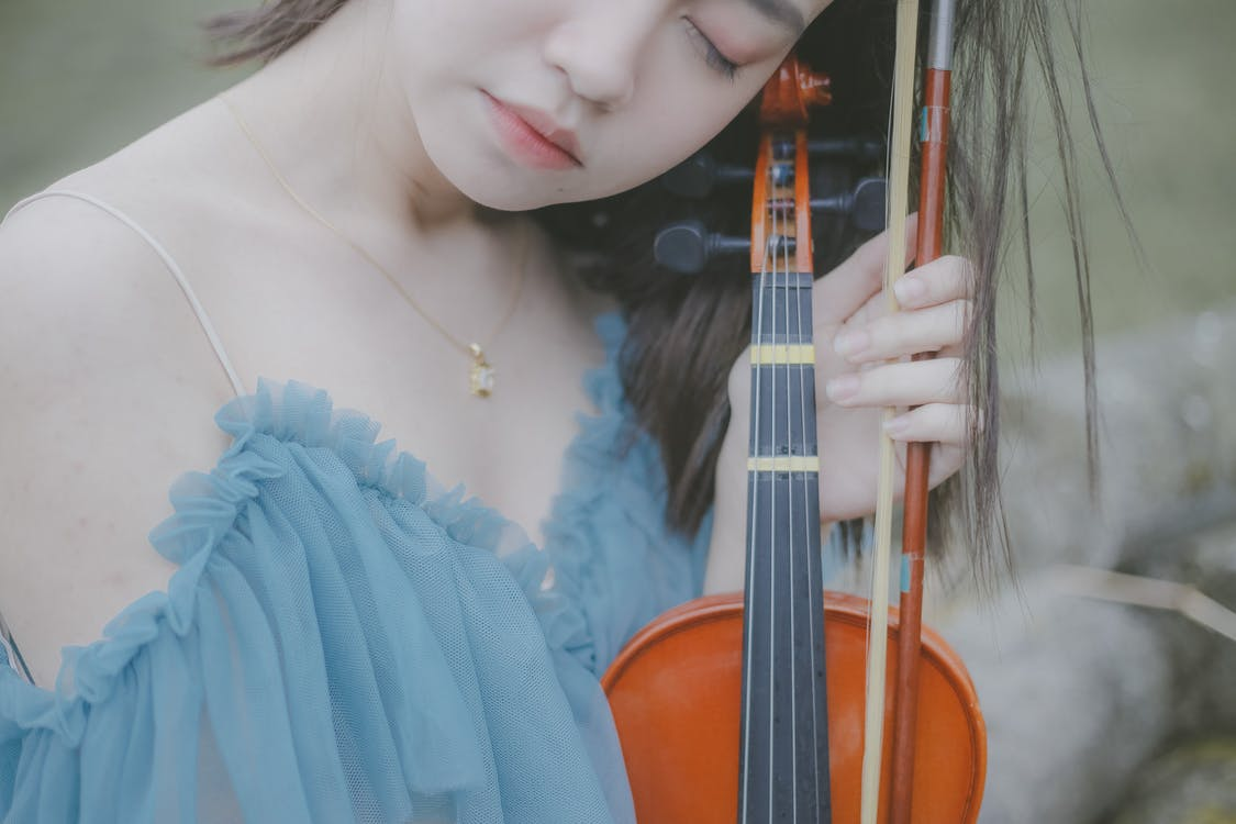 Close-Up Shot of a Woman Holding a Violin with Her Eyes Closed
