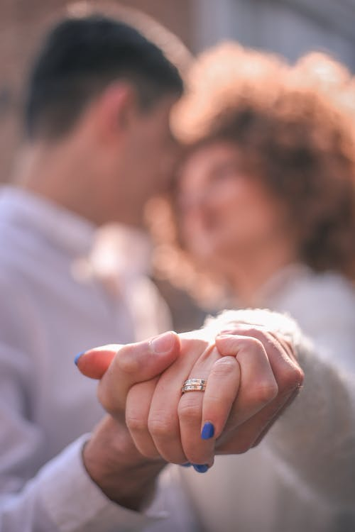 Soft focus of loving man and woman with engagement ring holding hands while dancing in sunlight