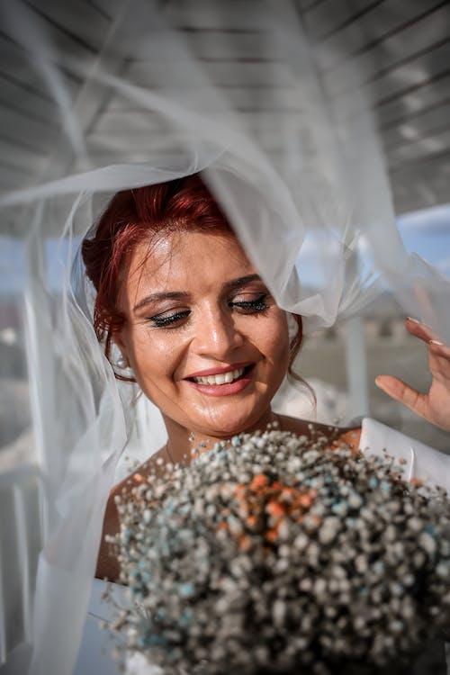 Cheerful bride with bouquet under veil