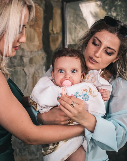 Mother with little baby in arms near friend