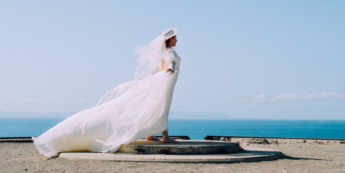 Woman in White Bridal Gown Standing in Brown Round Concrete Surface Under Blue Sky during Day Time