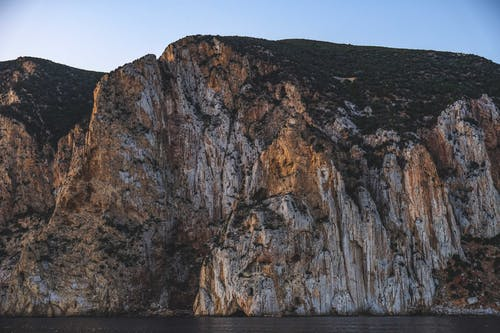 Rough stony steep cliff located on coast of rippling sea under cloudless blue sky