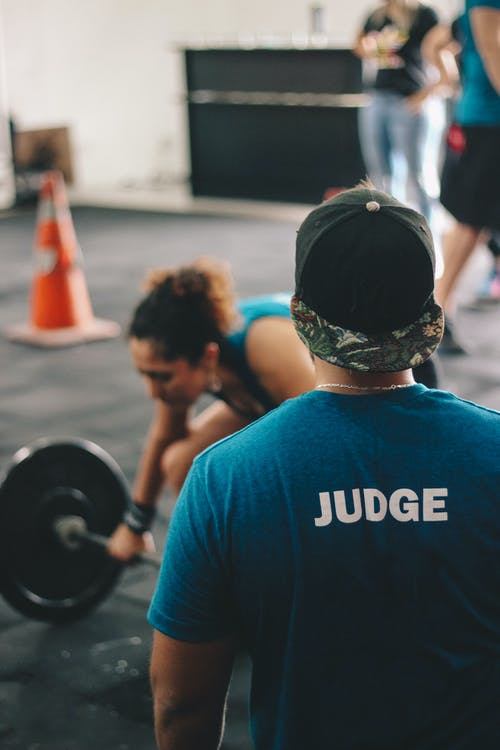 Man in Blue Crew-neck Shirt Staring At Woman Trying To Lift Barbell
