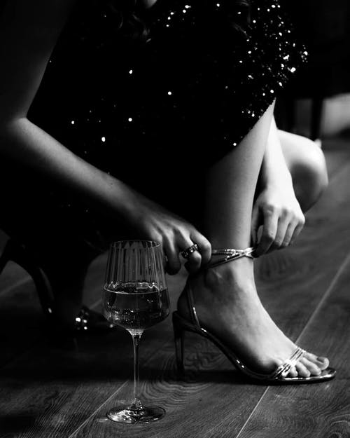 Faceless woman on high heels near glass with champagne