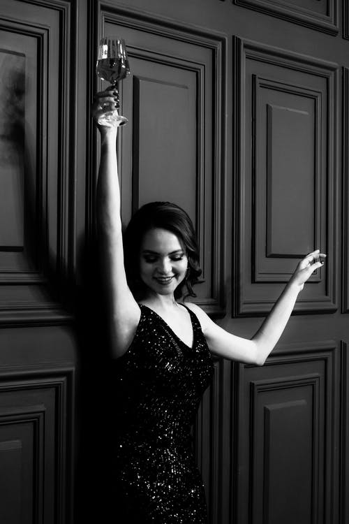 Happy lady in dress with raised hands and wineglass