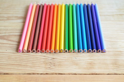Assorted-color Color Pencils on Brown Wooden Planks