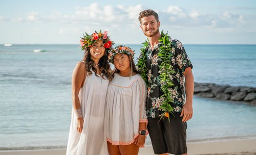 Happy young multiethnic couple and female friend in floral wreath hugging on sandy seashore and looking at camera
