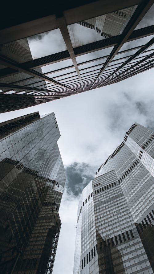 Low Angle Photography of High Rise Buildings Under Cloudy Sky