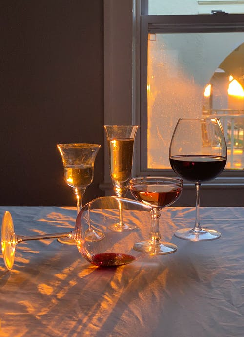 Glasses with alcoholic drinks placed on table in room in sunny day