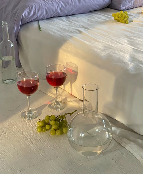 Glasses with wine near jar with water and bed