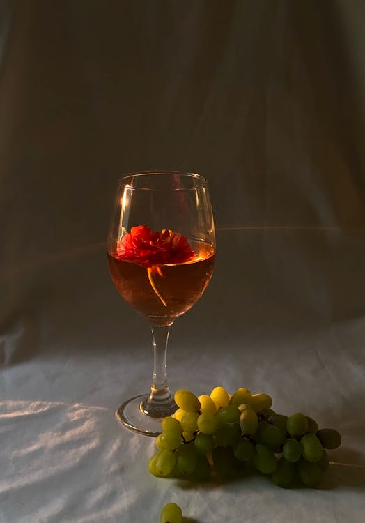 Transparent wineglass with alcoholic red drink and small flower placed on white creased fabric with fresh green grapes in studio