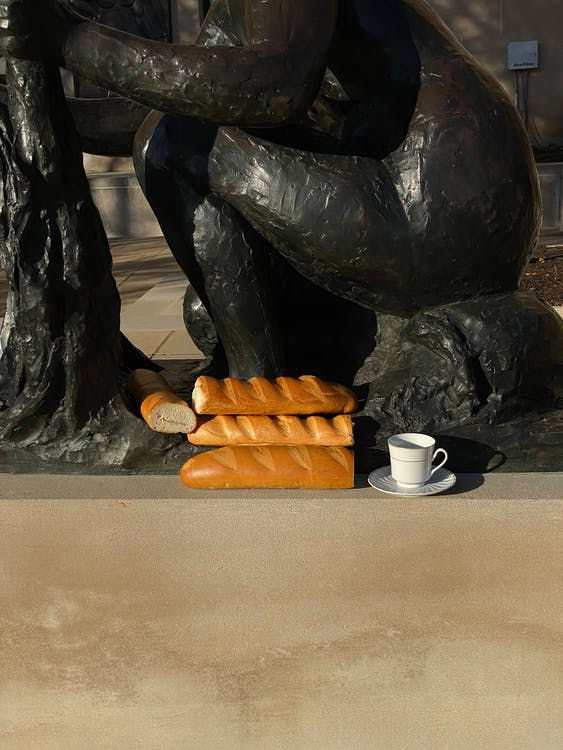 Fresh bread and coffee cup placed near statue on street