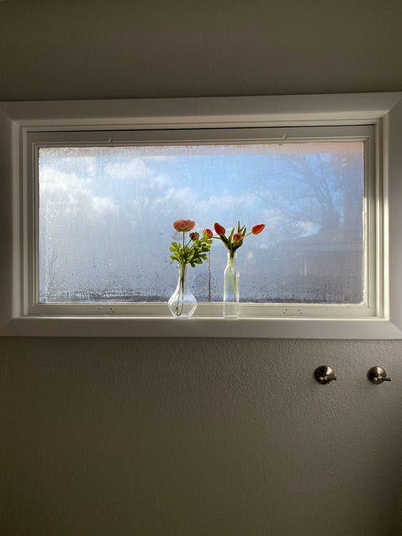 Elegant vases with fresh tulips placed on windowsill near misted glass in light apartment