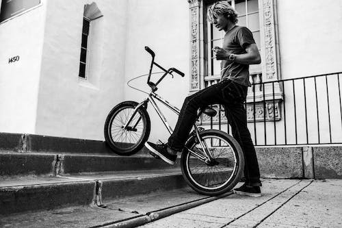 Man in Gray T-shirt Riding Bicycle in Grayscale Photography