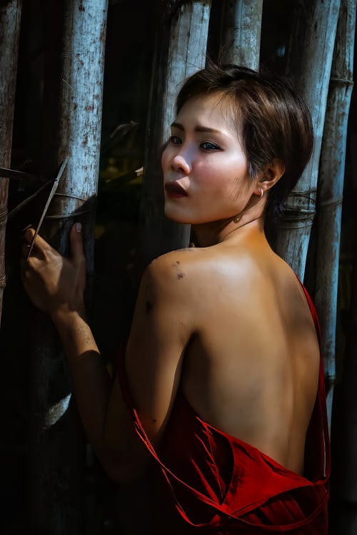 Ethnic lady in dress near bamboo trunks
