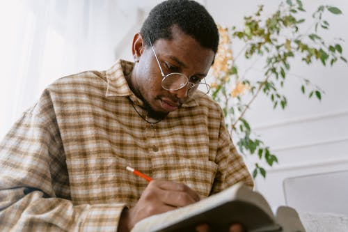 A Man Writing on a Book